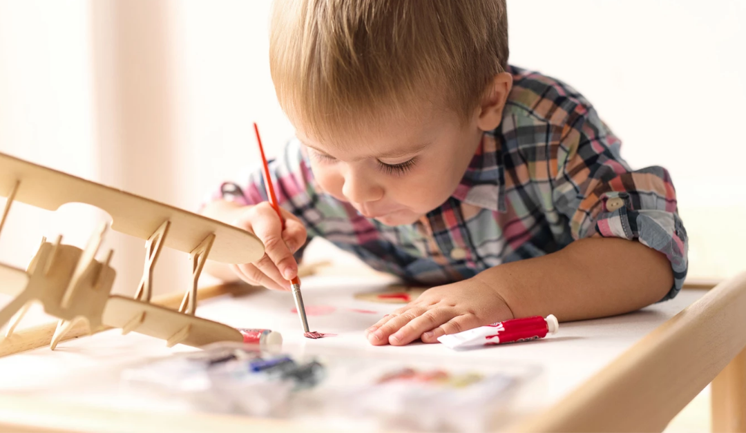 boy painting a wooden airplane